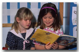 Two young girls reading the same book together.