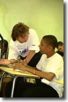 Picture of a para helping a student in the classroom.