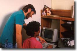 Picture of a para talking to a student who is using a computer.